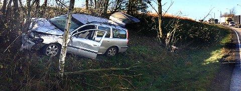 KJØRTE AV VEIEN: Denne Volvo stasjonsvognen kjørte av riksvei 111 og krasjet i et tre. I bakgrunnen sees deler av køen som oppsto i forbindelse med ulykken.
