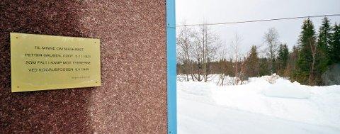 Minneplate om Petter på Ildgrubfossen kraftstasjon. I bakgrunnen bak bjørketrærne var tomta til maskinistboligen.