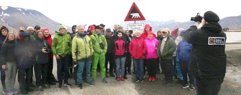 FARE FOR BJØRN: Helgelendinger på lesertur til Svalbard, foran et meget aktuelt skilt for tida; Fare for bjørn. Gjelder hele Svalbard. Guiden Wiggo Antonsen hjelper til med fotograferingen for mange i gjengen.