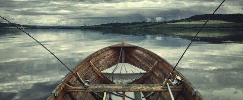 ENSOMT OG GODT: Jens Haugen er nyforelsket i sin gamle trebåt, fiskestengene og roen på vannet midt ute på Mjøsa. Foto: Jens Haugen