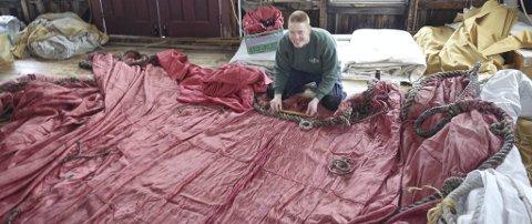 NOK Å GJØRE: Johan Tideland i Mystic Seaport reparerer «Drakens» seil. FOTO: «DRAKEN HARALD HÅRFAGRE»