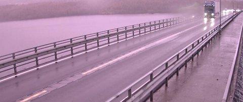 GRÅTT OG VÅTT: Det har kommet mye nedbør i Innlandet i løpet av natta og det vil fortsette å regne utover dagen.  Slik så det ut ved Mjøsbrua mandag morgen.