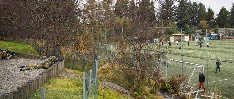 Alarmen går i den provisoriske basen i Olsvik. Alle mann til postene, med geværene klare. Nedenfor fortsetter fotballtreningen ufortrøden videre.