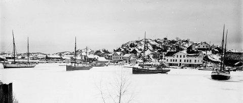 Frakteskøyter ligger frosset fast i Bysundet: Dette er et fotografi tatt tidlig på 1900-tallet. Fire frakteskøyter ligger innefrosset i Bysundet. Det er vinter i Kragerø og mye tyder på at isen ligger tykk i hele skjærgården. Da har ikke disse båtene annet å gjøre enn å vente på varmere tider, på at våren skal komme og at det igjen blir åpent vann.