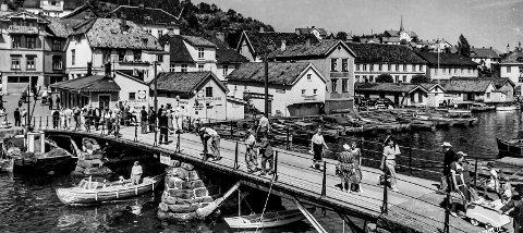 Bybrua 1950: Et av de mest stemningsfulle bildene som er tatt i Kragerø. Dette er Bybrua slik den var, hvilende på to brukar og med de velkjente grønne stagene på hver ende av brua. Midt på brua henger et skilt hvor det står «Sakte fart påbys». Bybrua var stedet hvor folk møttes, i hovedsak sjøfolk. Her kunne de stå og prate om skuter og båter de hadde seilet med. Her sto de og kommenterte det de så av motorbåter som kom og gikk, inn og ut av Blindtarmen. Bybrua var som en port til Kragerø, for på Dampskipsbrygga la kystruta til.