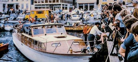 Bybrua og Jens Lauersøns plass: Dette gamle fargebildet er tatt i annen halvdel av 1960-årene. En større lystbåt har tatt seg helt inn til Bybrua hvor den fortøyer. Mange har samlet seg for å følge med på begivenheten. I bakgrunnen, på Jens Lauersøns plass var det parkeringsplasser. Ovenfor Asbjørnsens brygge står bilen til Einarson, som for anledningen er gul. Det hadde seg slik at Sturla, sønn til karikaturtegner Einarson, hadde sprøytemalt faren bil gul. Slik så den ut i et par år før den igjen ble rød.