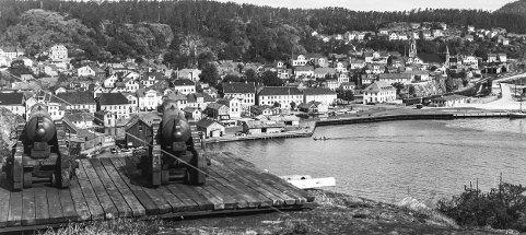 Kanonene på Veten: Dette fotografiet er tatt på 1930-tallet. Tidligere var lå et lite vakthus på Veten hvor det var brannvakt hver natt. Begynte det å brenne i byen skulle kanonene vekke folk. Siste gang det skjedde var da Skrubben Husmorskole brant i 1939. Da Norge ble invadert i april 1940, ble de gamle kanonene styrtet utfor heia. Byens myndigheter fryktet at byen skulle bli bombet hvis tyske fly fikk øye på de gamle kanonene. I dag er disse kanonene å finne på Gundersholmen kystfort.