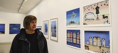 Mye blått: Marit Fåsetbru i Kongsberg kunstforening ser på bildene til Jan Baker. I bakgrunnen hengen bildene til Kjersti Næss. Mørke blåfarger går igjen i utstillingen.  Foto: Mona Sandviken