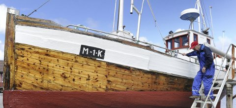 Båtpuss: Jan Sivertsen (78) pusser og steller den 75 år gamle treskøyta «Tor». Småbåthavna er kjærkommen for begge når skuta skal overhales over og under vannlinja. Foto: Roald Sevaldsen