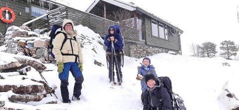 GODT HUMØR: Tone Cecilie, Sandra, Torjus og Jarand Krumsvik måtte  snurpe hettene sammen i snøværet på vei hjem fra hytta i Lyngsheia. Hytta på bildet er ikke deres, men en de passerer på vei hjem.
