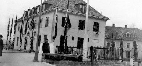 Venter på Kongen i 1927: Kragerø nærmer seg et helt spesielt jubileum. Om noen dager er det 90 år siden Kragerøbanen ble offisielt åpnet. I den anledning kom kong Haakon 7. til Kragerø. Som bildet viser var den nye stasjonsbygningen pyntet med lys rundt alle vinduene. Det var satt opp flaggstenger rundt bygningen og i enden av bygget, mot Blindtarmen, var det satt opp en musikkpaviljong. «Hele Kragerø» var på beina da kongetoget rullet inn foran stasjonen. Middagen ble holdt i skolens festsal på Feierheia.