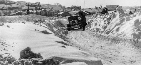 Blindtarmen 1954: Dette er et nytt fotografi som ble tatt senvinteren 1954, det som i ettertid har blitt omtalt som «den store snøvinteren». Fotografen har stått med ryggen til Jernbanestasjonen og foreviget en gammel bil som prøver å komme seg fram. De høye brøytekantene til høyre skjuler Blindtarmen. I bakgrunnen sees Øya. Eldre folk i Kragerø husker godt det som skjedde for over 60 år siden. Den gangen stanset hele lokalsamfunnet opp. Øyene ble isolerte, mat og medisiner måtte fraktes ut med helikopter.