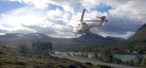 Et Sea King helikopter lander ved turisthytta Gjendesheim med en del av turfølget som gikk seg fast ved Besseggen onsdag kveld. De har overnattet i fjellet og kunne reddes ned først torsdag morgen. (Foto: Solrun Snilsberg)