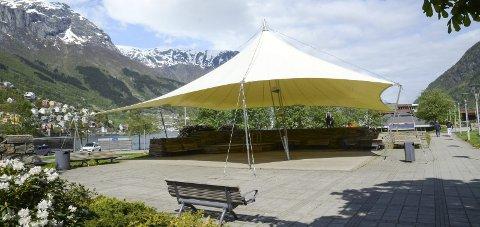 Almerkeparken: Seilduken i Odda sentrum må være den eneste «paraplyen» som gir fornemmelser av sol og sommer. Foto: Ernst Olsen