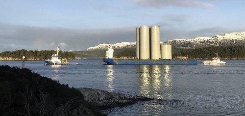 PÅ VEG SØROVER: Fem stålsiloar montert på ein lektar gjekk ut frå Westcon Yards i Florø med kurs for Karmsund og fabrikken på Husøy onsdag. Monteringa av siloane skal gjennomførast i løpet av månaden. Her er lekteren på veg forbi Nordnes.