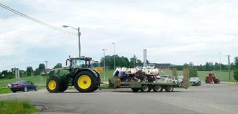 Med full henger: Det kan se ut som om det til sammen er 12 eller 13 personer på traktorhengeren gjennom rundkjøringen i Hof. Foto: Privat