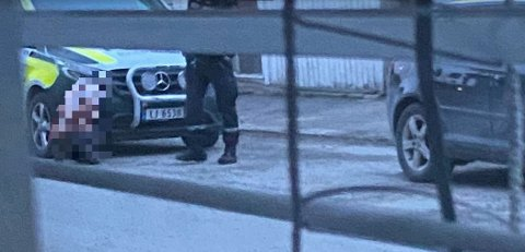 PÅGREPET: En polititjenestemann passer på den drapssiktede kvinnen som sitter på huk i gaten bare kort tid etter at ambulansen har kjørt vekk med den kritisk skadde mannen. Pågripelsen skjedde uten dramatikk.