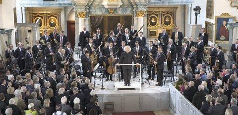 En verdensbegivenhet: Berlinfilharmonikerne med sin dirigent Sir Simon Rattle foran en fullsatt Røros kirke. Foto: Bjørn Nessjø