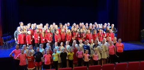 ALLE MED: På bildet er alle deltagerne som var på scenen under jubileumskonserten avbildet. Alt fra unge musikere og drillere til veteraner som ikke har spilt eller drillet på flere tiår.