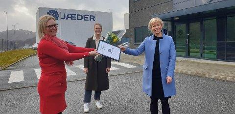 Guro Espeland hos Jæder mottar prisen for månedens klimabedrift fra NHO Rogaland-leder Tone Grindland. I bakgrunnen står marked-og bærekraftsjef Rakel Kyvik Wester.