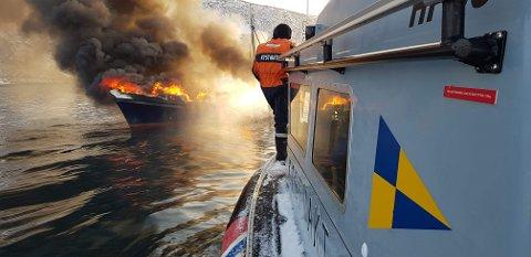 I FULL FYR: Sjarken som tok fyr utenfor Oksfjord i går formiddag sto ikke til å redde. Skipperen som var alene i båten, hoppet i havet og ble reddet av en annen båt.