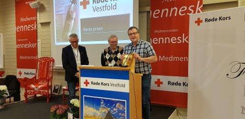 PRIS: Frode Berg Gustavsen (til høyre i bildet) og Tore Svenning (i midten) mottar «Panto-Prisen 2018» på vegne av Sandefjord Røde Kors. Prisen ble delt ut av fylkesleder Reidar Falkensten (helt til venstre).