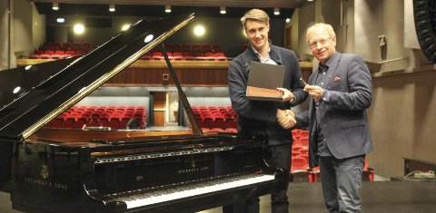 Nøkkel: Her overrekker Gisle Duas, daglig leder i Steinway Piano, nøkkelen til Bjørnar Mikkelborg. Nøkkelen brukes til å åpne det nye flygelet som har kommet til Narvik Kulturhus. foto: Mikael Marius Brendvik