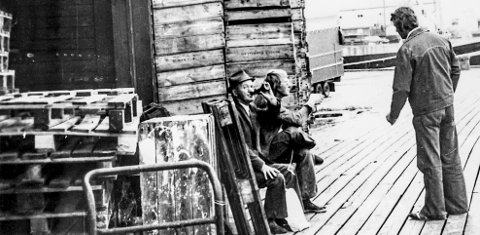 En øl på Dampskipsbrygga: Mannen med hatt som tar seg en øl, er en av Kragerøs mest kjente byoriginaler, «dikteren» Robert Nicolaysen fra Øya. Bak de gamle trekassene til fiskemottaket sees han sammen med to andre. Dette var et kjent sted der man i fred og ro kunne løse en rekke verdensproblemer. Dampskipsbrygga var selve det pulserende hjertet i Kragerø tidligere, den gang da kystrutas båter ankom Kragerø. To ganger på formiddagen ankom disse postbåtene, som de også ble kalt. En vestfra og en østfra.