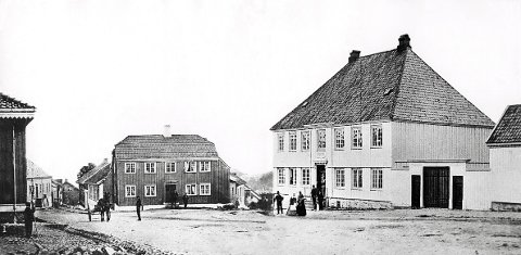 APOTEKET ØRNEN  i sin opprinnelig skikkelse på et bilde fra før 1869. Omtrent midt på bildet ser vi øvre del av Jochums og til høyre øvre del av Prinsegata. Bebyggelsen mellom disse to gateløpene ble utradert av en brann i 1869.