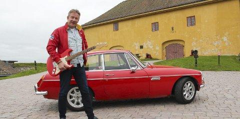 KJENT INNSLAG: Erik Øverby med sin røde MG 1972-modell – et kjent innslag i Kongsvinger sommerstid. Å arrangere konsert på festningen er en drøm han har. Den like røde gitaren, en Fender Stratocaster, er mest til pynt, bedyrer han.foto: KARI GJERSTADBERGET