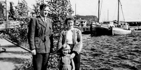 På Dampskipsbrygga 1955: Familien Brændhagen, Sverre, Susi og datteren Signe på den gamle dampskipsbrygga i Kragerø. På 1950-tallet var det fortsatt daglige anløp av kystruta, både østgående og vestgående rute. Det litt spesielle med dette fotografiet ser man bak familien. Brygga er pyntet med lautrær. Det ble gjort i forbindelse med feiringen av Kragerødagene hvor det var musikk, bryggedans og fest i Kragerø sentrum. Dette skjedde midt i juli måned.