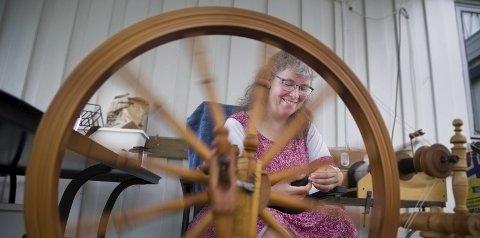 LAGER TRÅ: Unna Hallgren holder jevn fart på rokken, og mater ut en jevn trå fra den ferdige kardede mørkebrune ulla av spelsau.