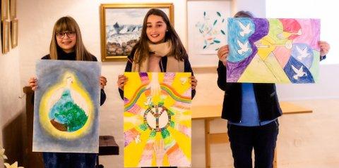 VINNERNE: De tre vinnertegningene presenteres av tegnerne, fra venstre Frida Elen (12) fra Åsgård skole, Enkela Aliu (12) fra Brønnerud Skole, og tegningen til Sivert Ødegård Engen (12) fra Kroer skole. Da Sivert akkurat var på leirskole ble hans tegning presentert av Grete Skrede fra Lions Ås/Eika.