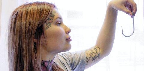 1 kork: Denne kroken fikk Connie med seg hjem som et suvenirer etter hun var på suspension i Oslo.     2 Implantat: Connie er frisør av yrke og liker ting med stil. På hånden har hun et implantat av et hjerte under huden.    3 Stress: Connie Lindberg tømmer hodet for stress ved å henge i kroker. Foto: PRIVAT   5 Penere: Noen mener Connie hadde vært penere uten alle tatoveringene. Til det vet hun ikke hva hun skal si.   6 Tatoveringer: Med synlige tatoveringer, også i ansiktet, er Connie Lindberg lett å kjenne igjen.