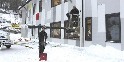 SNØRYDDING: Robert Nøklegård i lift og Stian fra kommunen rydder snø fra taket til Brevik oppvekstsenter.