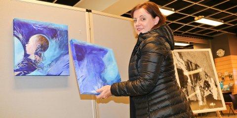 """Torsdag ettermiddag var Siri Anette Berge Syvaldsen i gang med å henge opp bildene til utstillingen """"I en stall, i en gåte""""."""