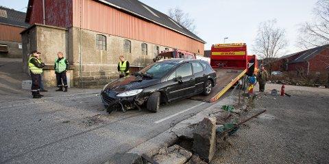 Personbilen havnet på taket etter å ha kollidert i gjerdet (til høyre i bildet).