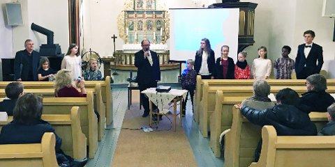 INTRODUSERT: Kantor Bjørn Vidar Ulvedalen presenterte elevene sine. Helt til venstre ser vi panfløyte-solist Roar Engelberg. Konserten ble vist på skjerm foran i kirken.