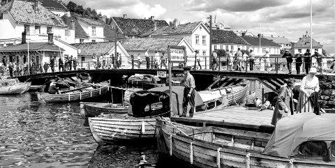 Skyssbåt-sentralen tidlig på 1960-tallet: Bildet viser Bybrua og livet i Blindtarmen for snart 60-år siden. Det er mange folk på Bybrua. Noen står og betrakter livet på sjøen, andre haster over brua. Den gangen holdt Skyssbåt-sentralen til på den ene siden av brua og på den andre siden hadde familien Johansen sine skyssbåter, «Marna», «Swift» og «Fram».