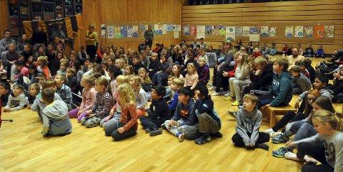 Full aula: Hele barnetrinnet var tilstede i Aulaen når vinneren av konkuransen skulle kåres. Legg merke til alle de flotte tegningene som henger bak i rommet.