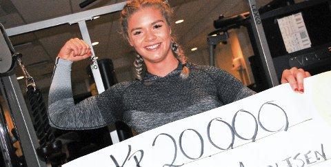 FIKK ET LØFT: Styrkeløfter Isabell Adolfsen viser strålende fram sjekken som forteller at hun har blitt tildelt Høland og Setskog Sparebanks idrettsstipend for 2018. – Kjempeoverraskende, men gøy og veldig inspirerende, sier 19-åringen, som er innstilt på å vise enda mer muskler framover i karrieren. Foto: Øivind Eriksen