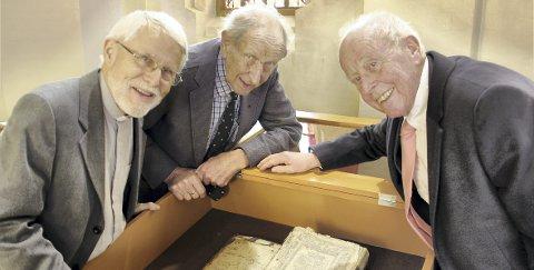 BIBELSTUDIER: Sogneprest emeritus Pål Sindre (t.v.), Hans Hernæs og Bjørn Hernæs studerer det unike bibeleksemplaret som nå er tilbake i Strøm kirke, i glassmonter.BILDER: SIGMUND FOSSEN