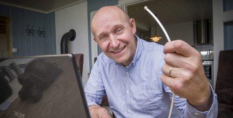 Fornøyd: En blid og fornøyd odøling, Trond Sundby, sitter ved stuebordet og sjekker nettkapasiteten på PC'n. Nå kan alle i familien være på nettet samtidig uten problem. Inne i kabelen han holder i hånda ligger den hårtynne glasstråden som gir dem en ny nett-hverdag.   BILDER: JENS HAUGEN