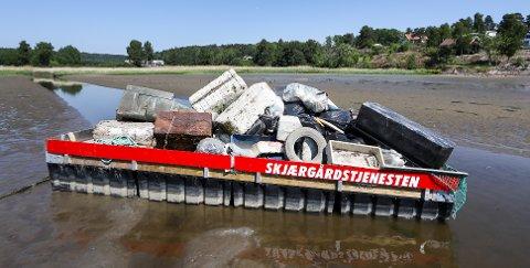STORE MENGDER: På en flåte i Sonskilen ligger et gammelt rustent skap, bildekk, store isoporblokker, sekker med søppel, flere store plastkanner og et parafinfat. Skjærgårdstjenesten har ryddet i fjæra.