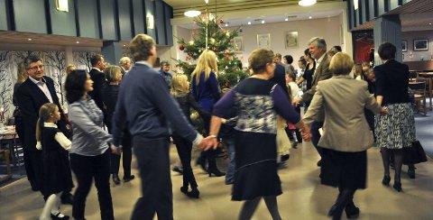 JULETREFEST: Både store og små går rundt juletreet under IOGTs årlige juletrefest. Dette bildet er tatt fra juletrefesten for drøyt fire år siden. Selv om det ikke er like mange folk til stede som i «gamle dager», pleier rundt 60 personer å ta turen til Globusgården hvert eneste år. Arkivfoto Janne Grytemark