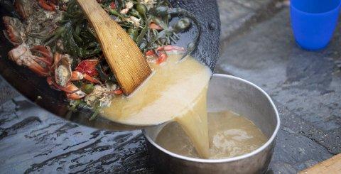 De svarte krabbene lir røde etter å ha frest i woken. Kraften blir en herlig suppe når fisken er satt til.