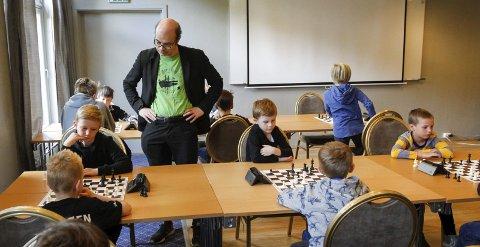 REKRUTTERING: Hans Olav Lahlum syns Mosjøen sjakklubb har gjort en strålende jobb med rekruttering. Fredag formiddag var det barnesjakkturnering, og Lahlum var innom og studerte spillerne. Foto: Per Vikan