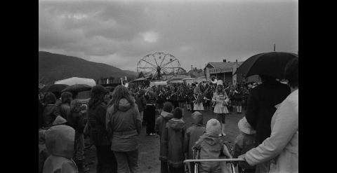 TIENDEBYTTEVÆR: Regn, folk og korps preget åpninga av Tiendebytte i Mosjøen i 1974. I år ser det bedre ut - yr.no lover oppholdsvær og solgløtt.