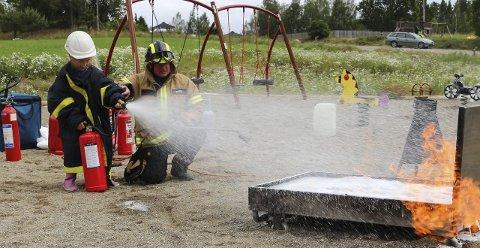 Stas: Både små og store fikk prøve seg som brannmenn i Aremark på Åpen brannstasjon. Dette bildet er fra fire år siden. Her er Maylinn Stubberud (7) i aksjon.  Lars Frode Bjørk passer på.