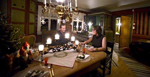 TRIVELIGE TIMER: Olav og Jona Evju på gården i Flesberg. Rundt dette bordet pleier de å sitte i jula når de har besøk av venner og familie. I hjørnet av stua, bak Jon er det en gammel skapseng, som kan brukes til overnatting hvis den som skal sove der ikke har for lange bein.